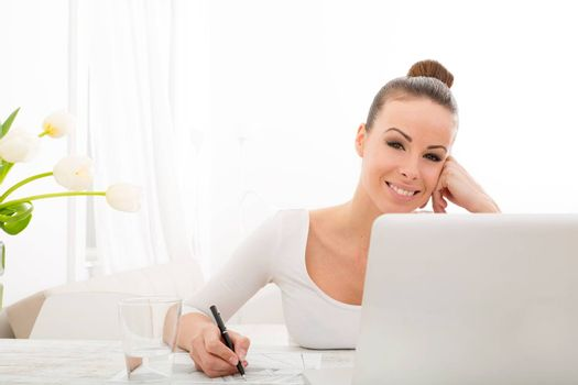 A young adult woman drawing an architectural plan at home with laptop and flowers.