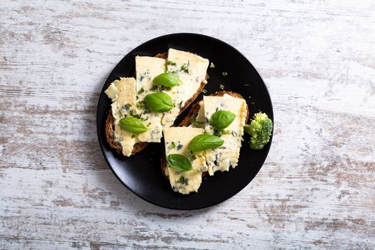 European style sandwiches with Roquefort cheese and Basil leaves on dark bread.