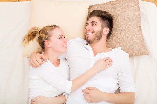 A happy young couple hugging in bed.