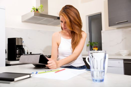 Portrait of a redhead girl holding a tablet pc in the kitchen.
