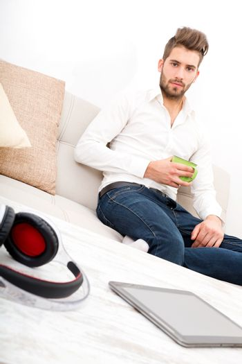 A young adult man sitting on the couch holding coffee.