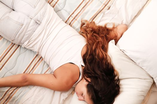 A young woman sleeping on the bed.