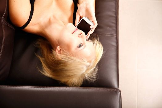 A blonde girl talking with a smartphone.