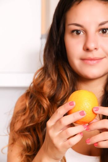 A young adult woman with fruits in the kitchen.
