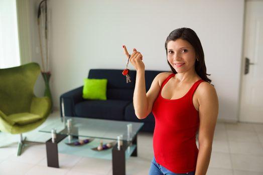 Portrait female home owner smiling holding keys new house