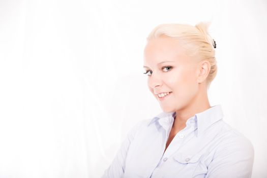 Portrait of a young blonde secretary in a white office.