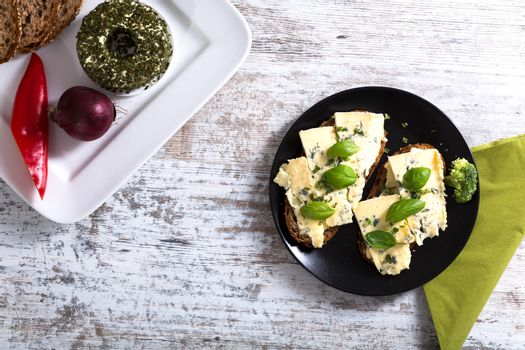 European style sandwiches with Roquefort cheese and Basil leaves on dark bread with some ingredients on the side.