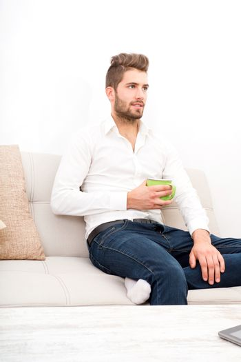 A young adult man sitting on couch with coffee.