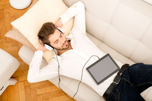 A young handsome man on the couch listening to music.