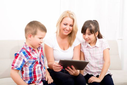 A mother using with her son and daughter a Tablet PC.