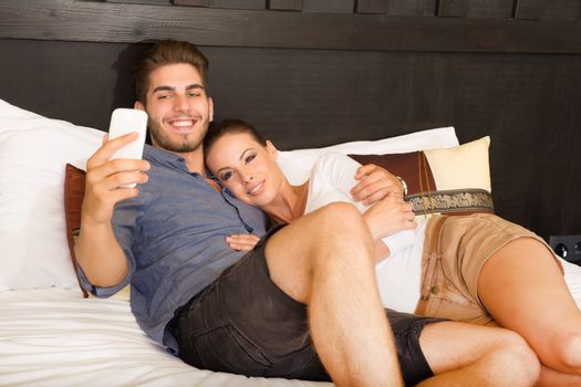 Young couple using a smartphone in a asian hotel room while lying on the bed.
