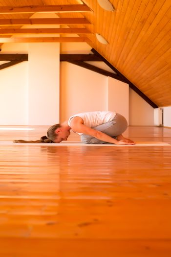 A young Woman practicing Yoga in a large attic Studio.