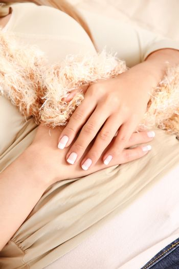 A pretty young woman showing her white nails.