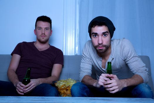 Two Friends watching passionately TV with Beer and Potato Chips.