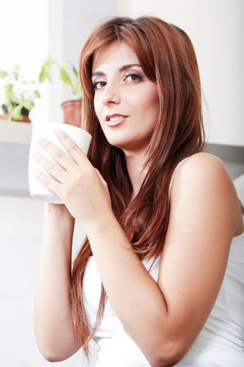 A young adult woman sitting in the kitchen with a cup of coffee.