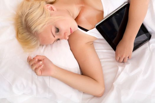 Portrait of a blonde girl sleeping in a bed holding a tablet pc.