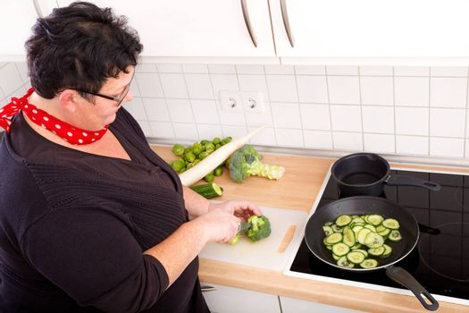Mature overweight woman cutting vegetables in the kitchen.