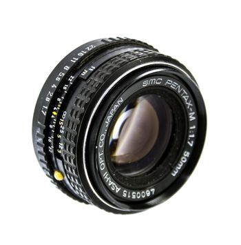 An old manual control camera lens isolated on white.