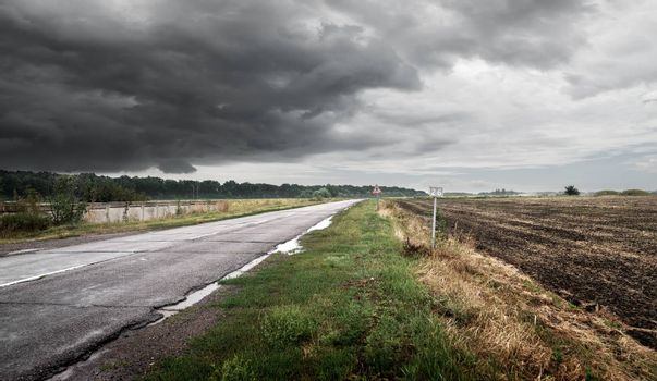Road in cloudy weather against thunderclouds