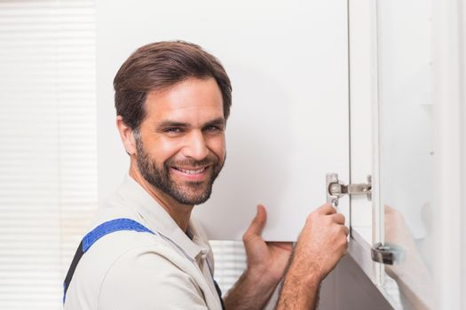 Handyman fixing the cupboard