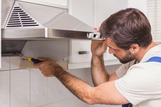 Handyman fixing the oven