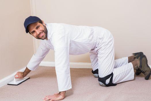 Handyman laying down a carpet