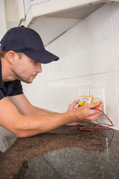 Electrician metering voltage with digital multimeter