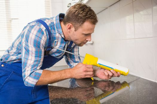 Plumber putting filling in between tiles