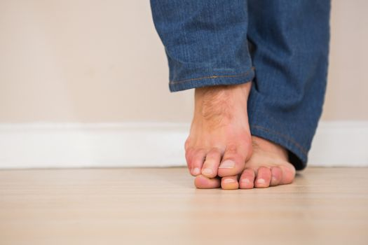 Mans bare feet on wooden floor