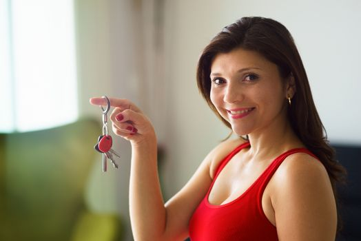 Portrait woman home owner smiling holding keys new house