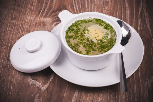 Chicken noodle soup in white plate with egg