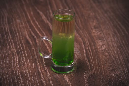 green layered alcohol shot cocktail on wooden background