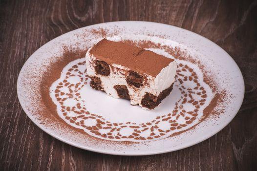 tiramisu dessert slice on white plate with cacao