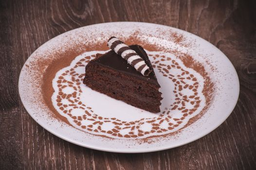 Chocolate cake slice on white plate with cacao