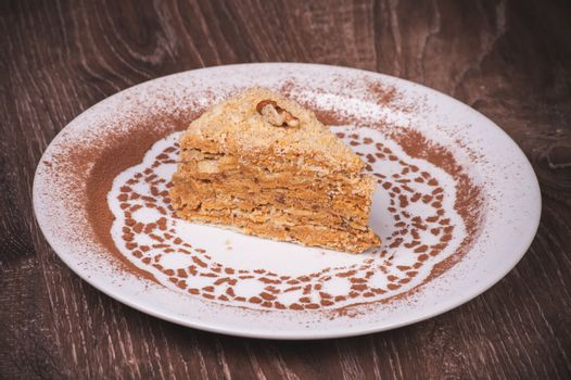Nut cake slice with honey on white plate