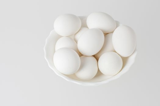 White eggs in a bowl on white background