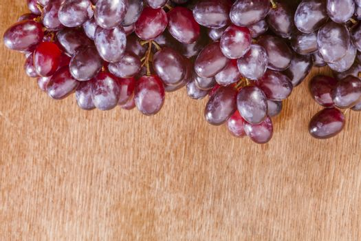 bunch or red grapes on a wood surface