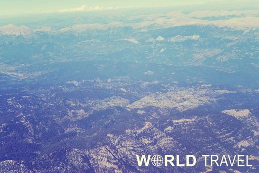 Aerial view of mountainous. wooded. snow-covered terrain. Inscription World Travel and related symbol