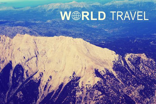 Aerial view of mountainous terrain with high ridge. Iinscription World Travel and related symbol