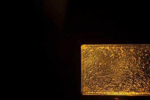 One kg gold bullion bar 999.9 on plain black background