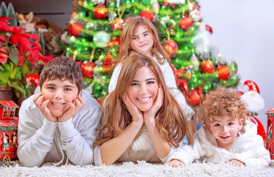 Happy Christmas celebration, cheerful family having fun at home, lying down near beautiful decorated Christmas tree, love and happiness concept