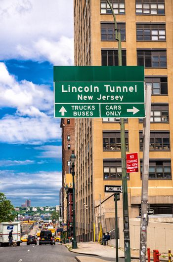 Lincoln Tunnel signage in Manhattan with city skyline