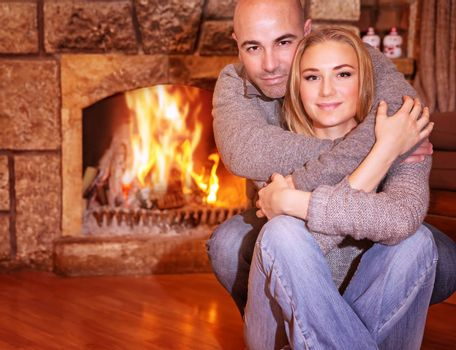 Portrait of gentle couple sitting near fireplace at home, romantic celebration of Christmas holidays, love and togetherness concept