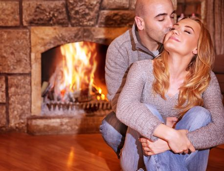 Portrait of gentle couple sitting near fireplace and kissing on luxury ski resort, romantic celebration of Valentine day, love and togetherness concept