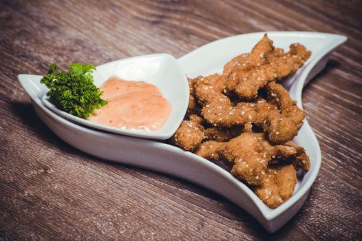deep fried chiken breast strips on white plate