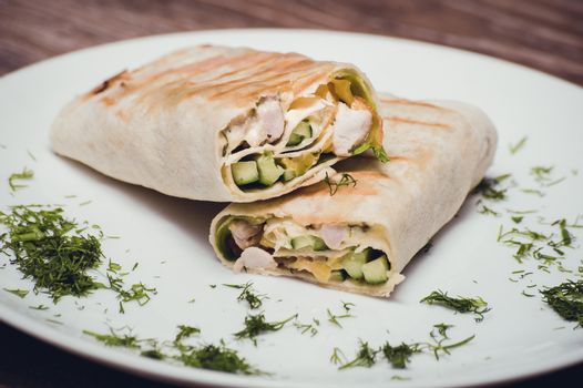 chicken and avocado fried wrap on white plate