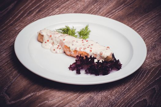 salmon fillet with caviar cream sauce on white plate