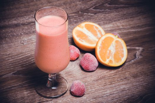 strawberry orange smoothie in high glass with fruits