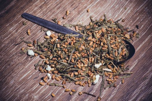 dried herbal tea on spoon on wooden background