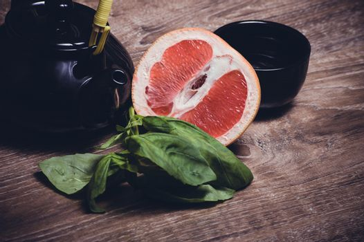 grapefruit and basil tea served in cup with teapot